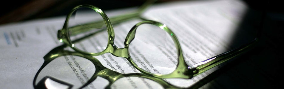 Reading glasses resting on typed pages