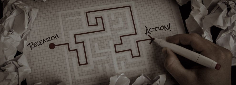Hand drawing through a maze from 'Research' to 'Action'